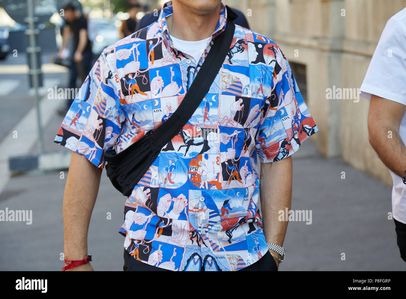 92b8927b4 MILAN - JUNE 17: Man with comics in blue and red colors on tshirt before  Prada fashion show, Milan Fashion Week street style on June 17, 2018 in  Milan