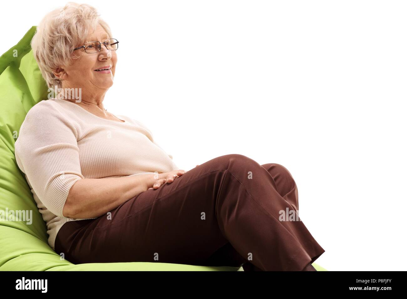 Elderly woman sitting on a beanbag isolated on white background - Stock Image