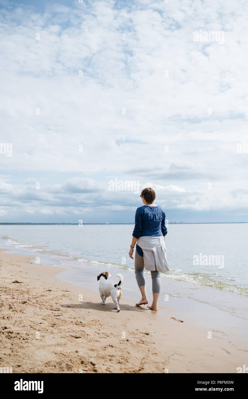 Woman walking with her dog on the sandy beach. Rear view. - Stock Image