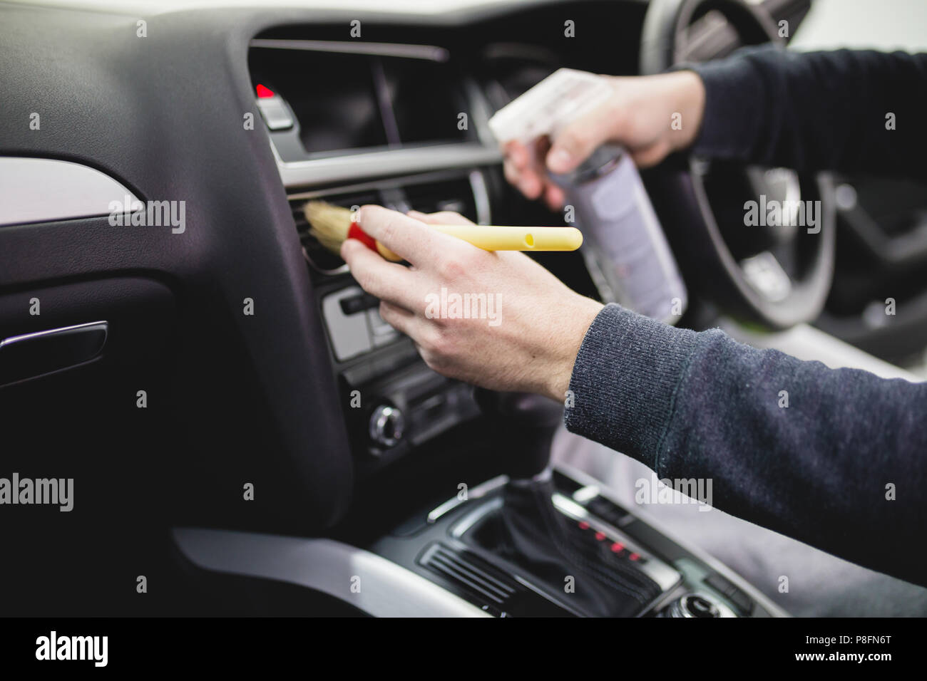 a man cleaning car interior, car detailing (or valeting) concept