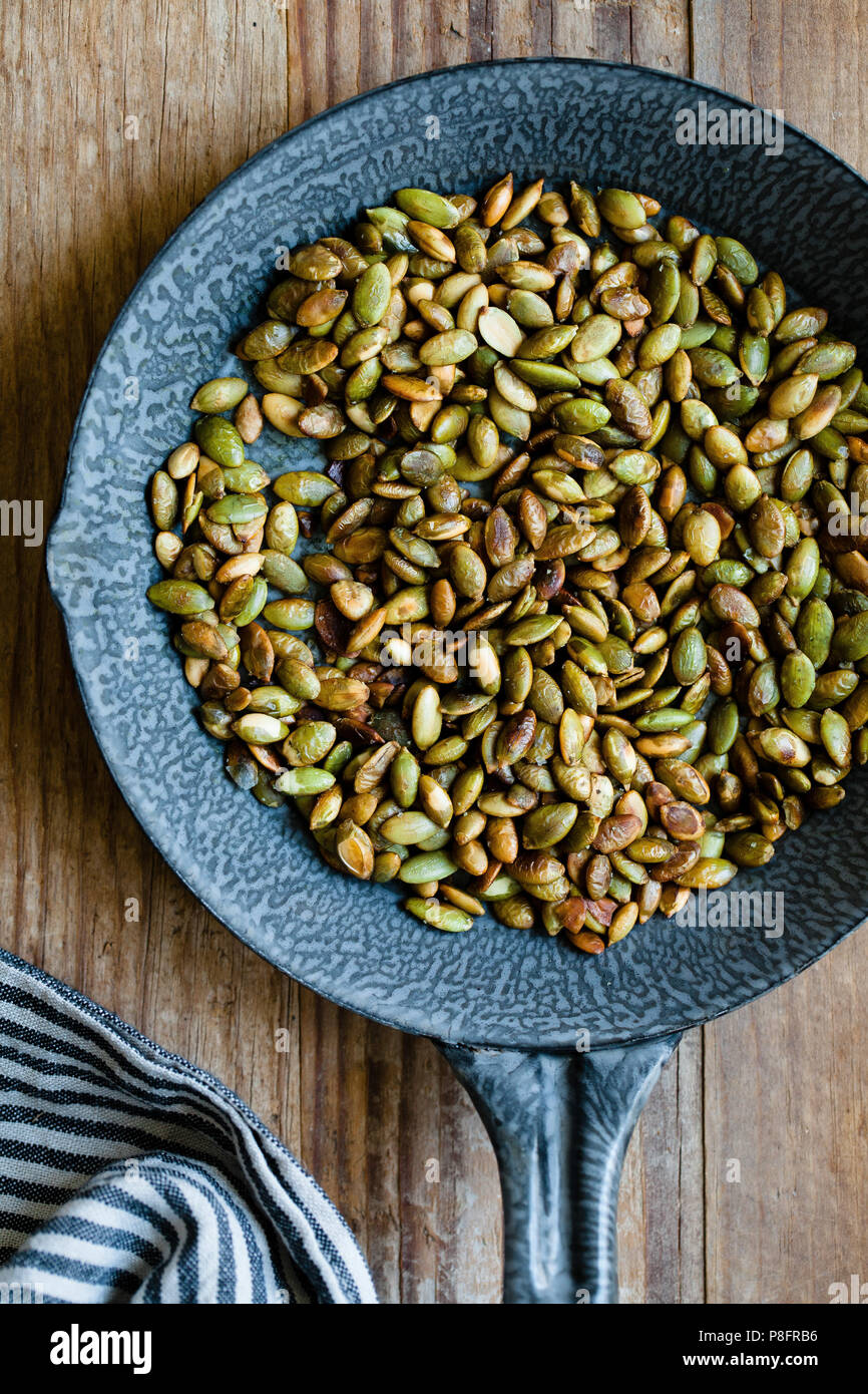 Toasted pumpkin seeds in pan - Stock Image