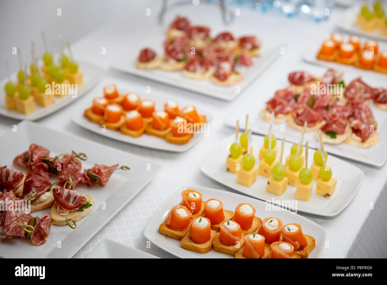the buffet at the reception. Assortment of canapes. Banquet service. catering food, snacks with salmon - Stock Image