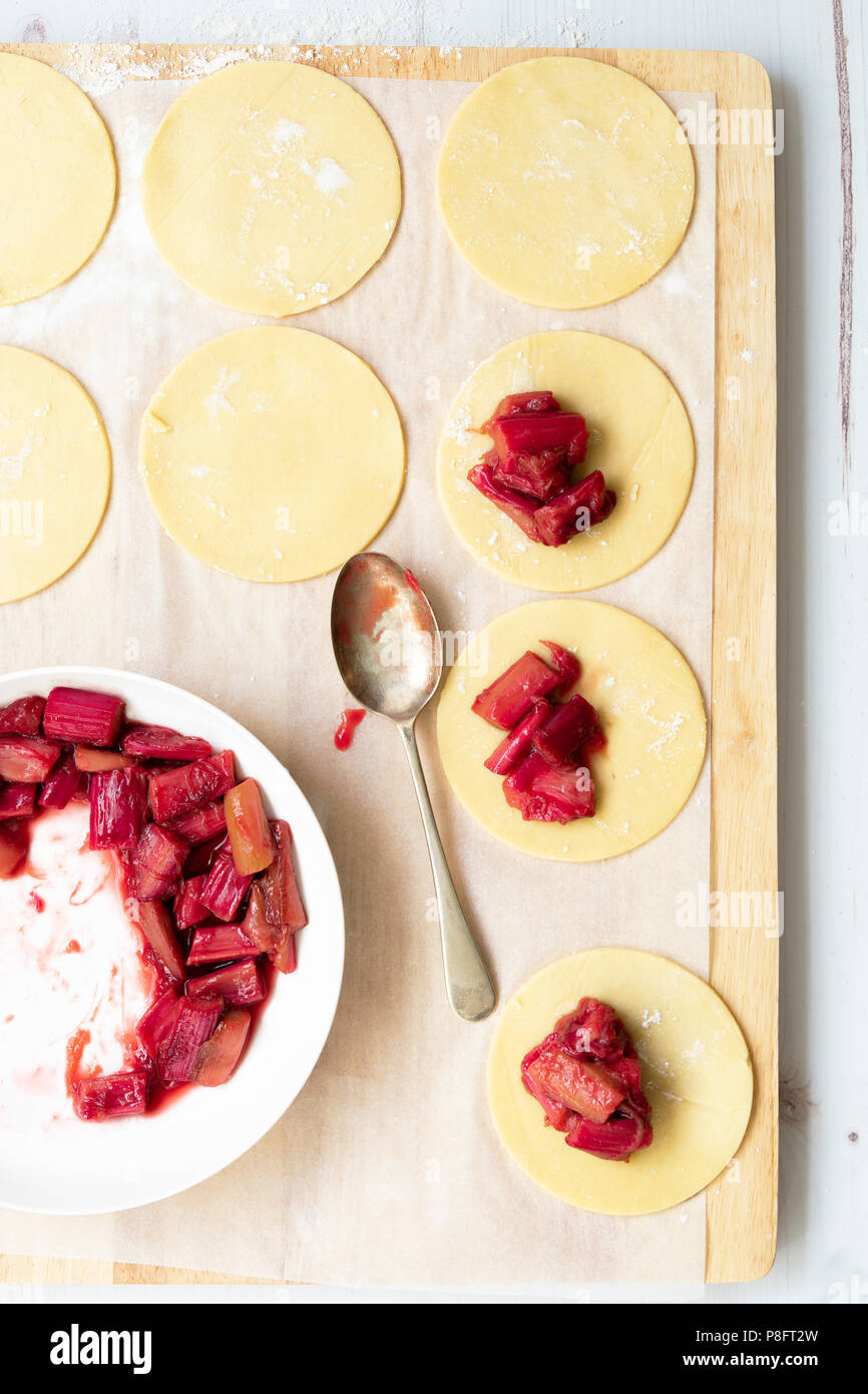 Shortcrust pastry rounds filled with a spoonful of roasted rhubarb. - Stock Image
