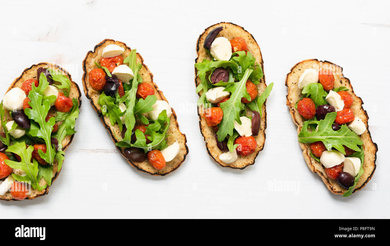 Roasted cherry tomatoes, black olives, bococcini, and rocket leaves on chargrilled bruschetta bases. - Stock Image