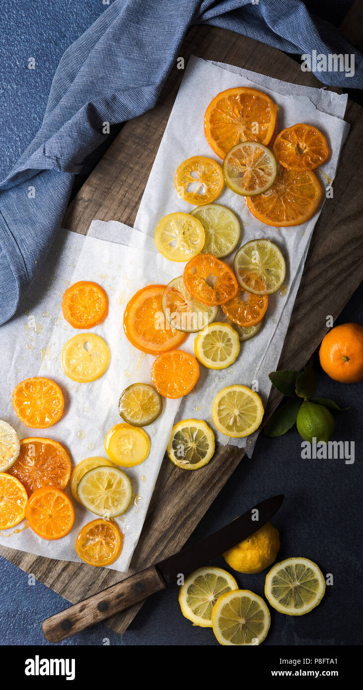 Candied orange, lemon and lime slices with a knife on a wooden cutting board. - Stock Image