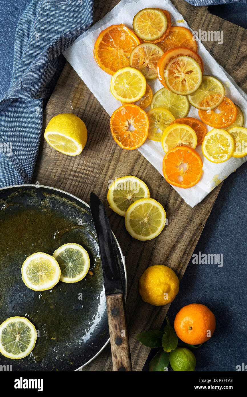 Candied orange, lemon and lime slices cooking in a pan and cooling on baking paper. - Stock Image