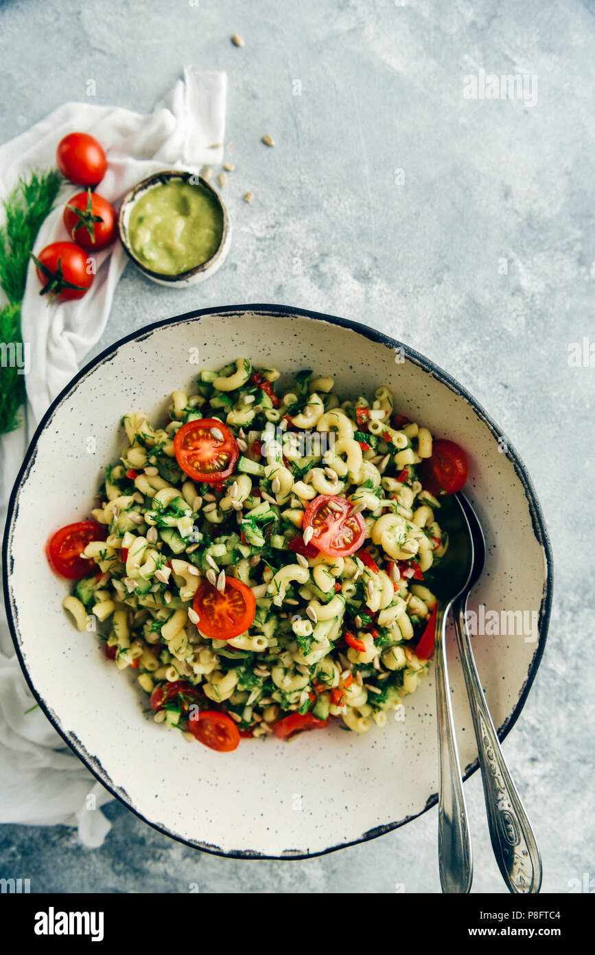 Vegan pasta salad with avocado dressing served in a handmade ceramic white bowl with two spoons on the side. - Stock Image