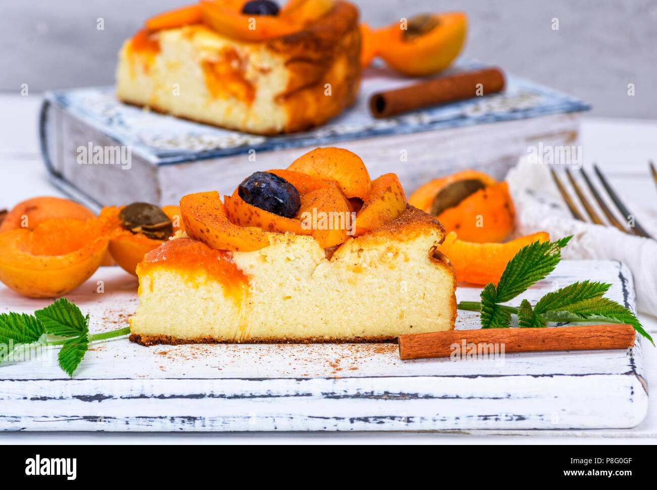 piece of cheesecake with apricots on a white wooden board, close up - Stock Image