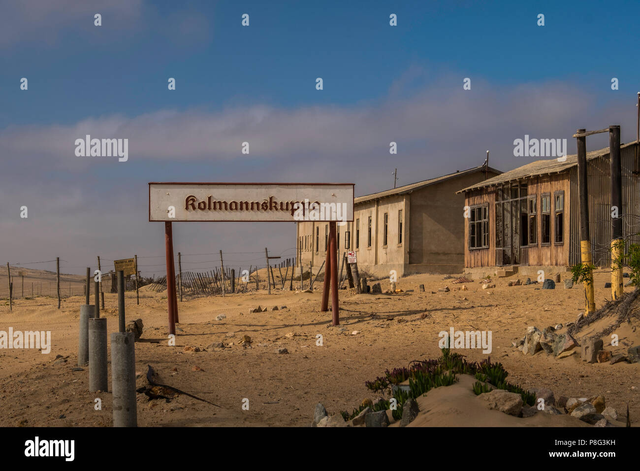 Kolmannskuppe, German spelling of Kolmanskop, sign with abandoned buildings in ghost town of former diamond mining community in the Namib Desert of Na - Stock Image