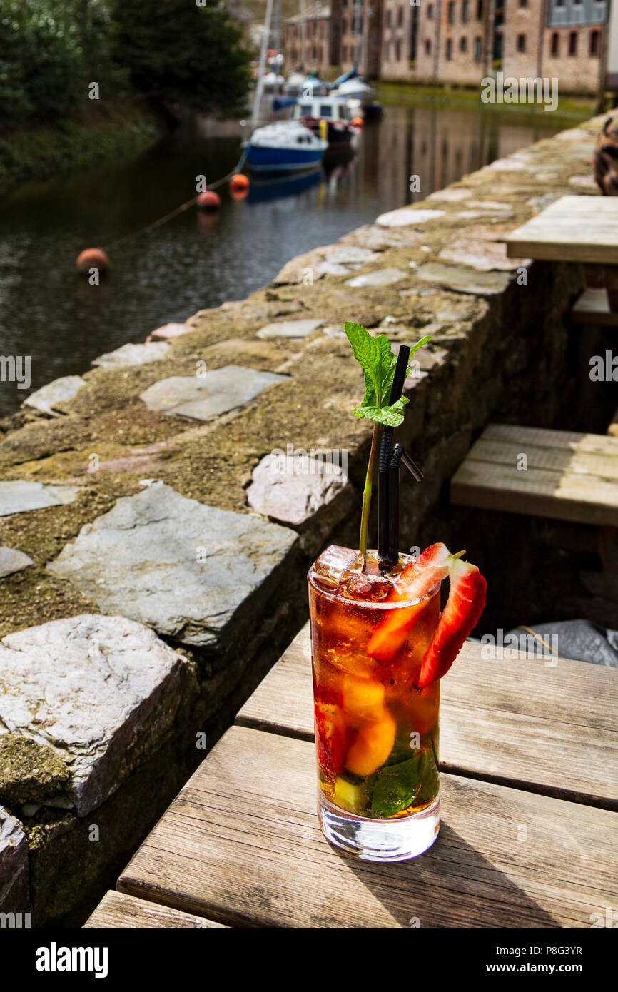 A Pimm's in a glass on a wooden table - a mint sprig like a tree - Stock Image