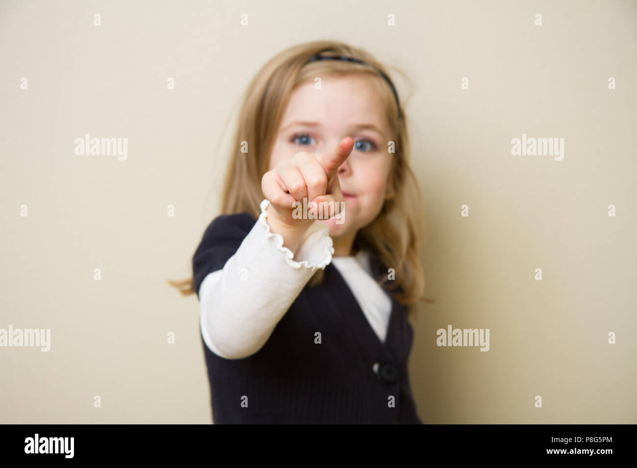 Young child holding her hand up pointing into the air. Focus is shallow and centered on the hand and finger of the child - Stock Image