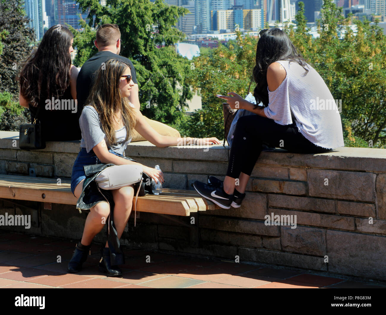 Young women chatting and relaxing at a park, enjoying the Seattle skyline view and the good weather. - Stock Image