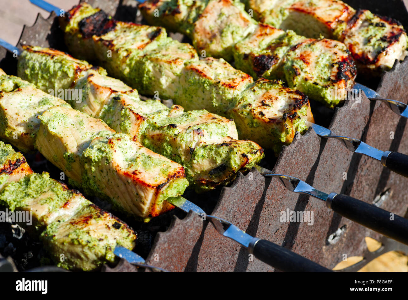 Skewers with pork meat under vegetable sauce - Stock Image
