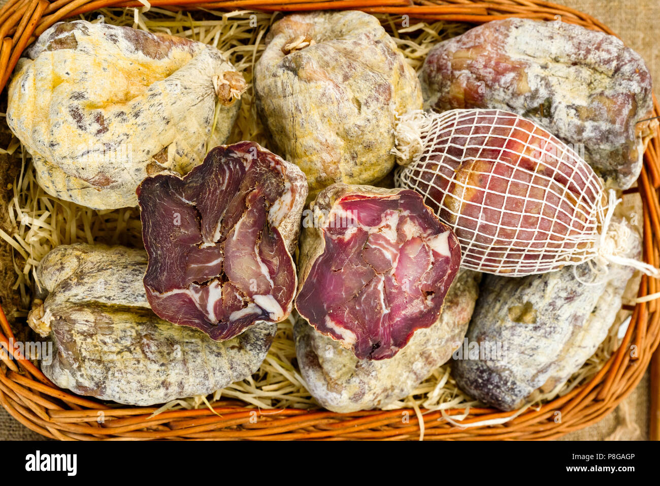 Raw smoked meat in a wicker net - Stock Image