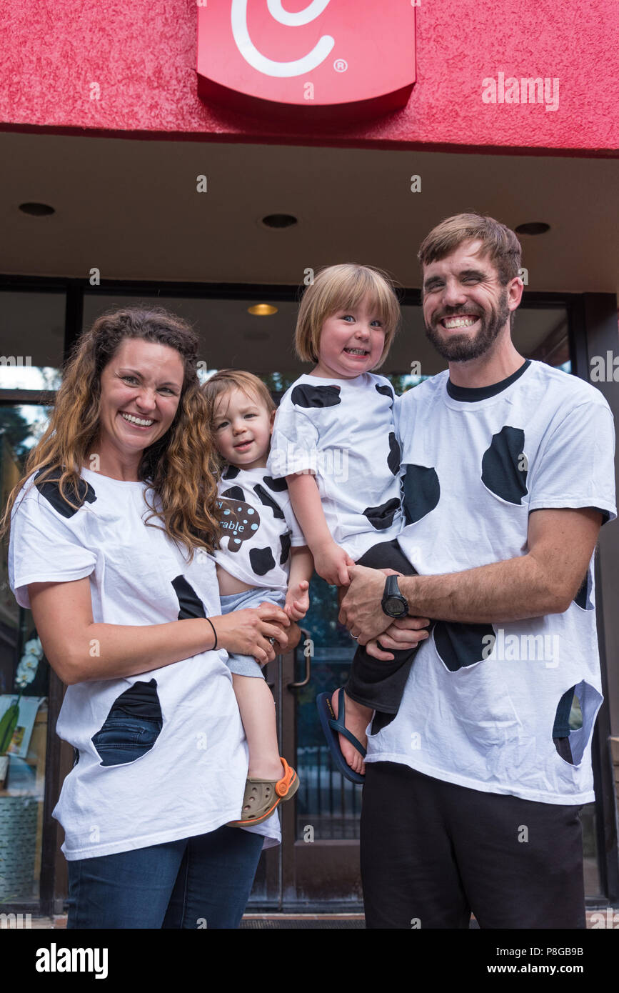 A happy family with their homemade cow outfits for Cow Appreciation Day at Chick-fil-A, America's top-rated quick service restaurant. (USA) - Stock Image