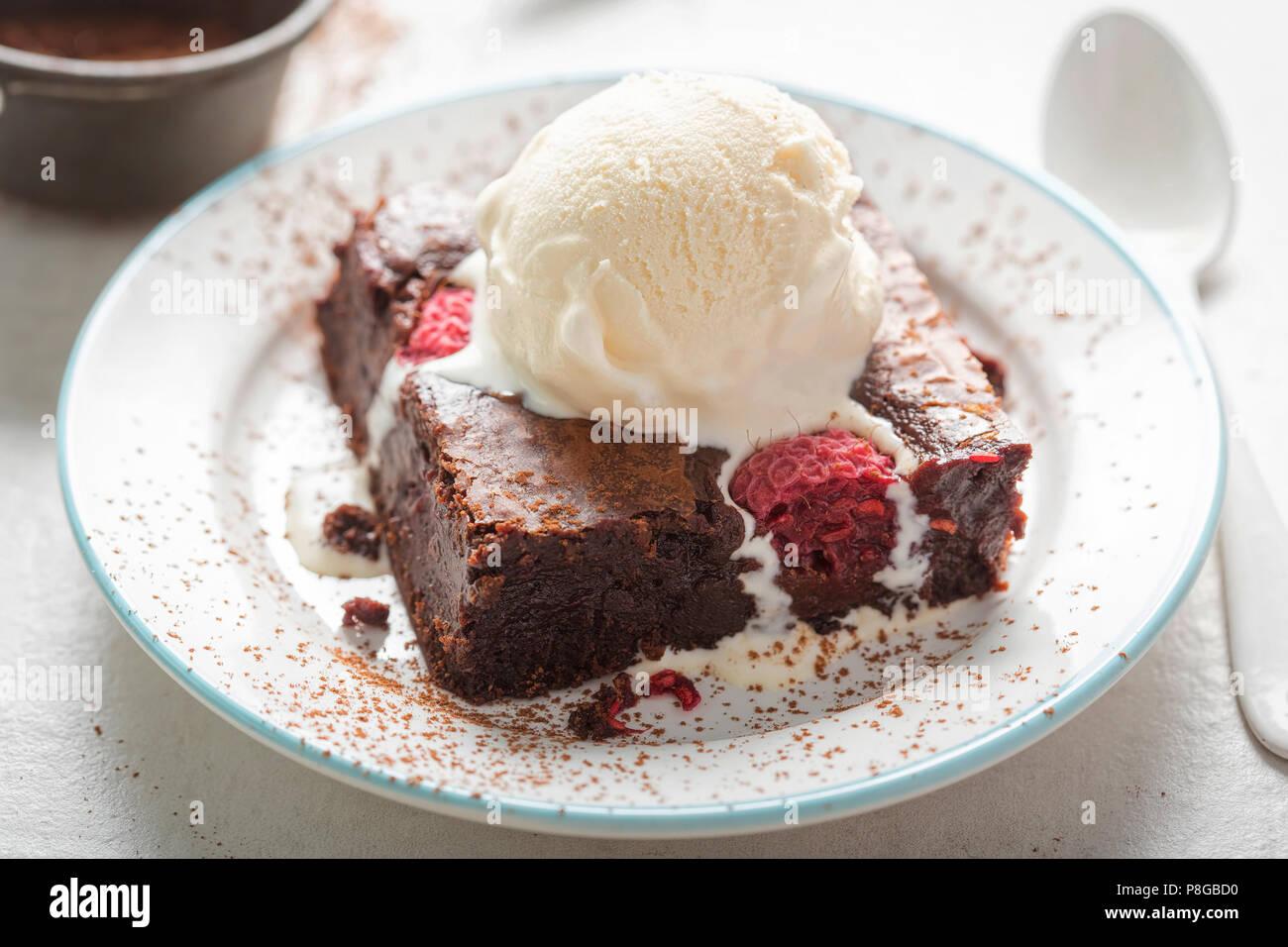 Raspberry chocolate brownies with vanilla ice creams - Stock Image