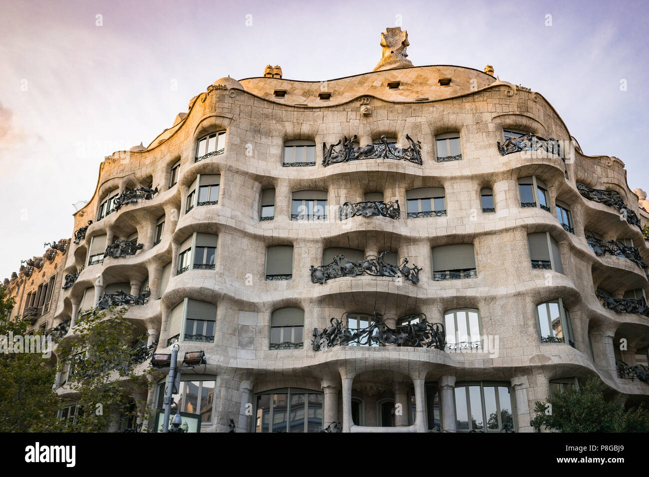 Waves and sculptural building details of La Pedrera, Casa Mila in Barcelona, Spain. Ornate architecture, view from below at sunset, vibrant colours. Stock Photo