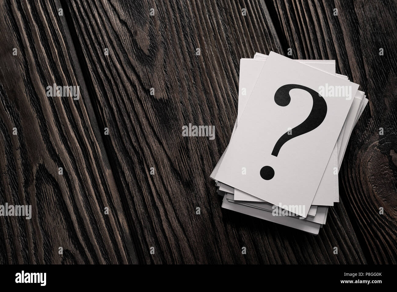 Stack of question mark cards on the wooden table with copy space - Stock Image