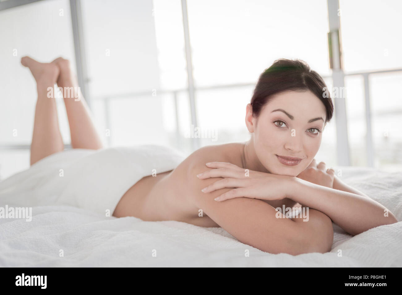 Shirtless woman lying on bed Stock Photo