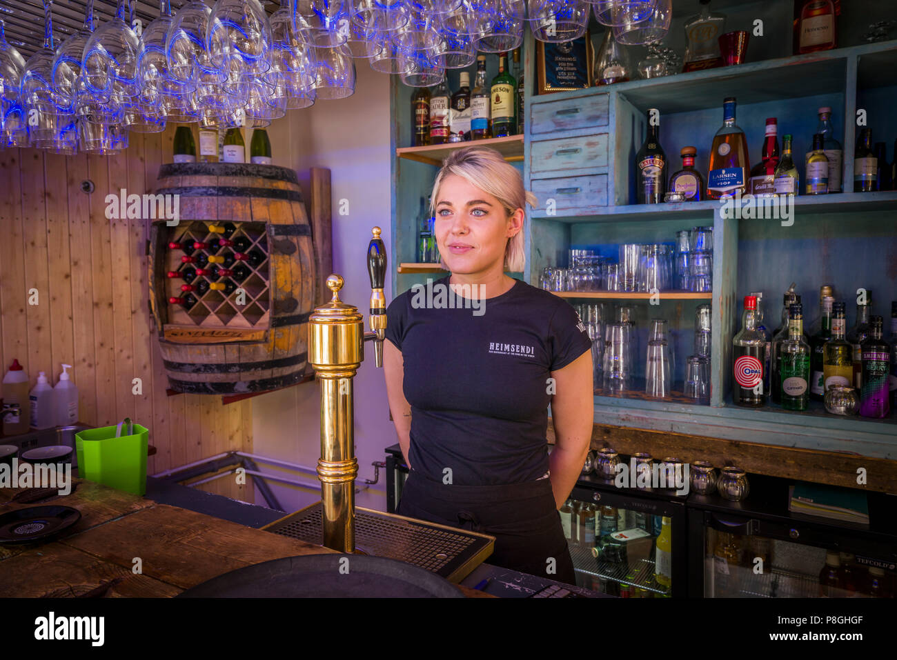 Woman working at a restaurant in Patreksfjordur town, West Fjords, Iceland - Stock Image