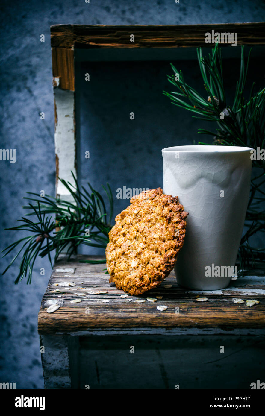 Thin honey and oat cookie with greenery and ceramic cup. - Stock Image