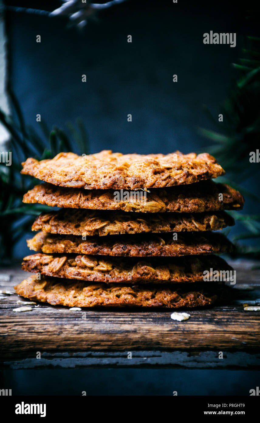 Thin honey and oat cookies stacked with greenery. - Stock Image