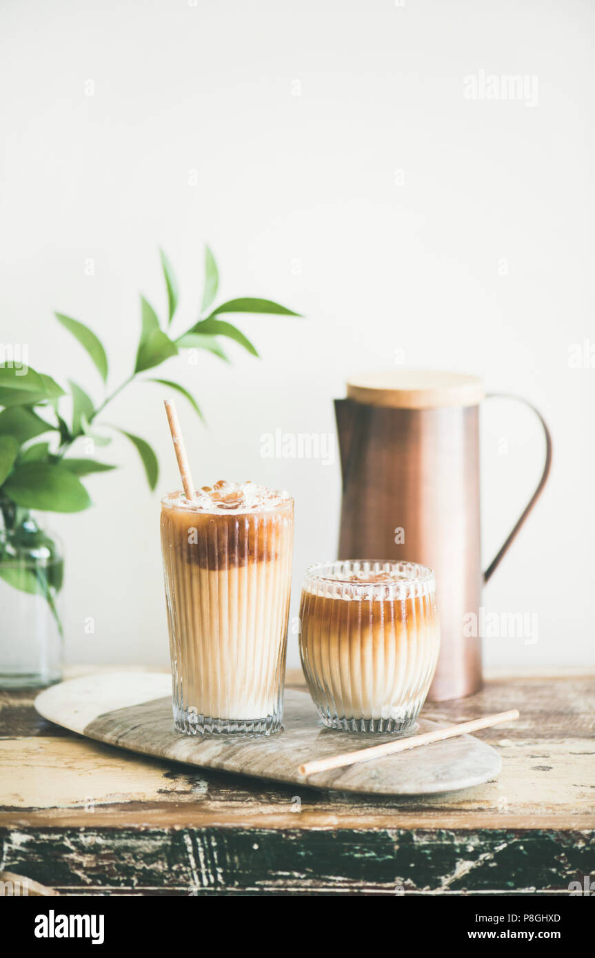 8efa9c58fd8 Iced coffee in tall glasses with milk and straws on board over rustic  wooden table, white wall, jug and plant branch at background, copy space.  Summer