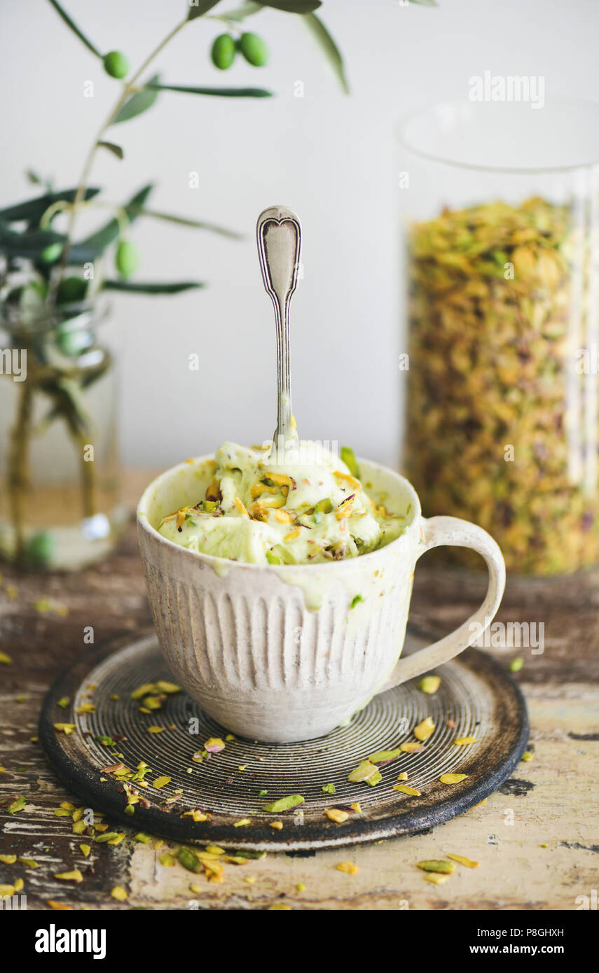 Homemade pistachio ice cream in ceramic mug with green pistachio nuts on rustic wooden kitchen counter, vertical composition. Summer refreshing ice cr - Stock Image