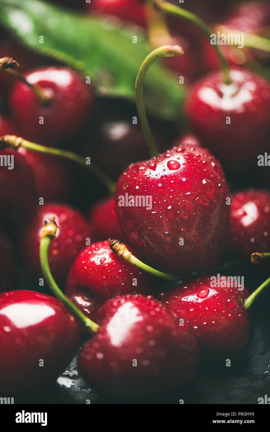 Fresh sweet cherry texture, wallpaper and background. Wet sweet cherries with leaves on dark background, selective focus, close-up, vertical compositi - Stock Image