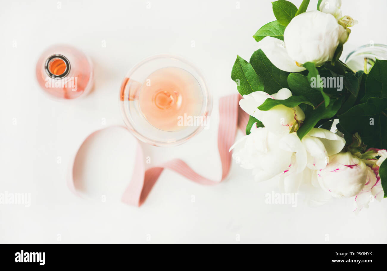 Flat-lay of rose wine in glass and bottle, pink decorative ribbon, peony flowers over white background, top view, horizontal composition. Summer celeb - Stock Image