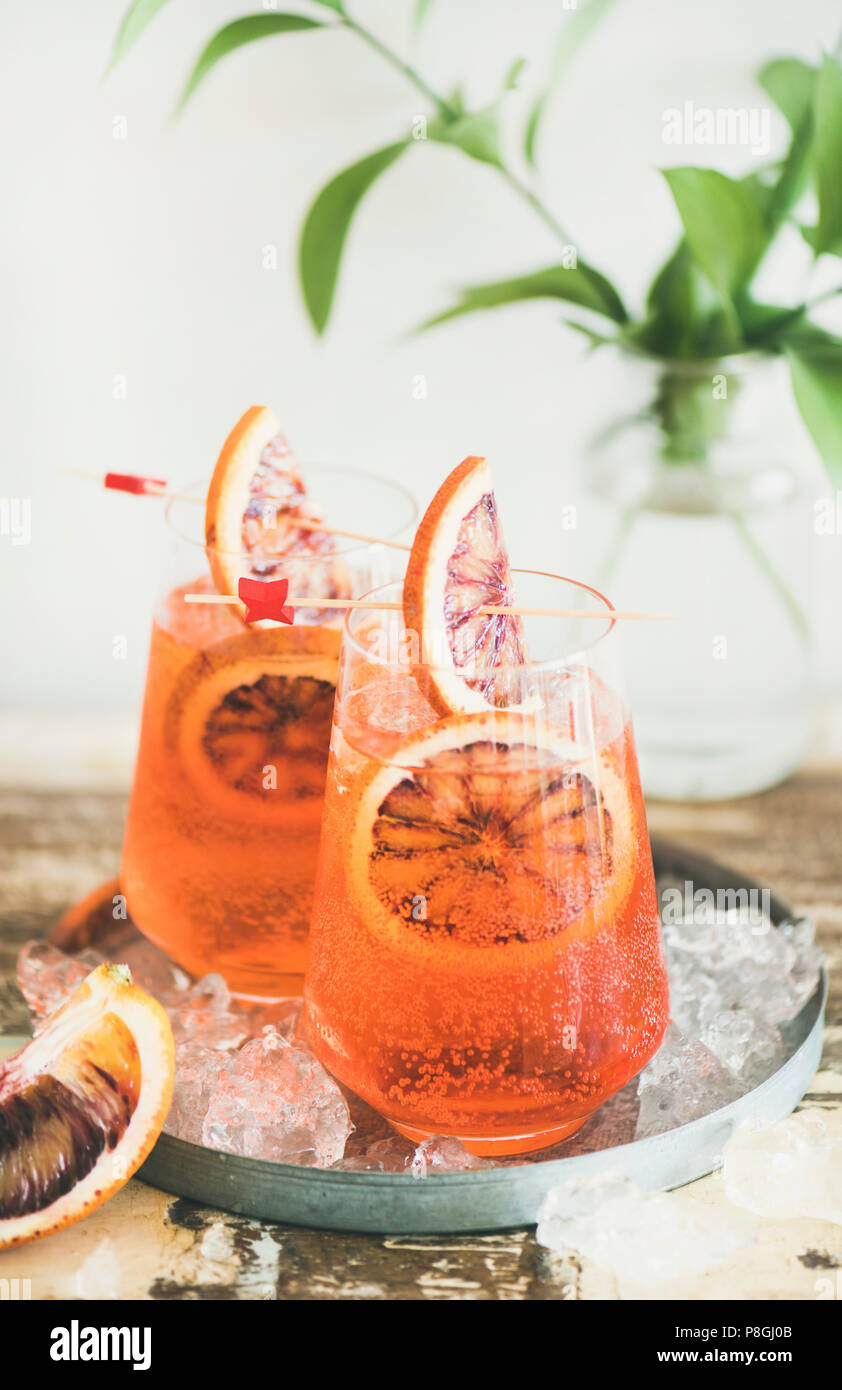 Italian Aperol Spritz alcohol cocktail with ice and blood orange slices on table, vertical composition. Traditional Aperol Spritz cocktail. Summer ref - Stock Image