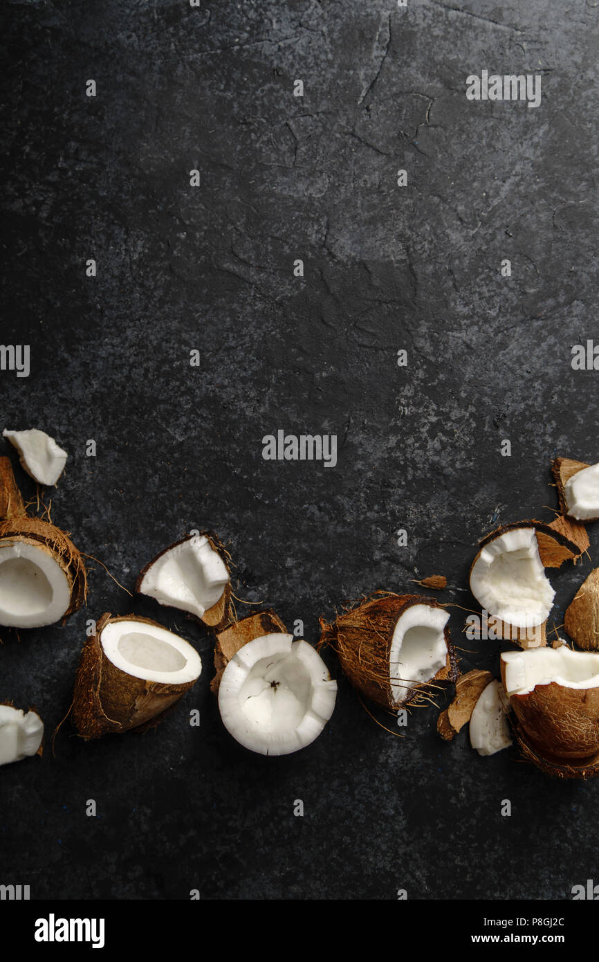 Cracked coconut arranged on dark textured background. Vertical flat lay with copy space. Soft light. - Stock Image