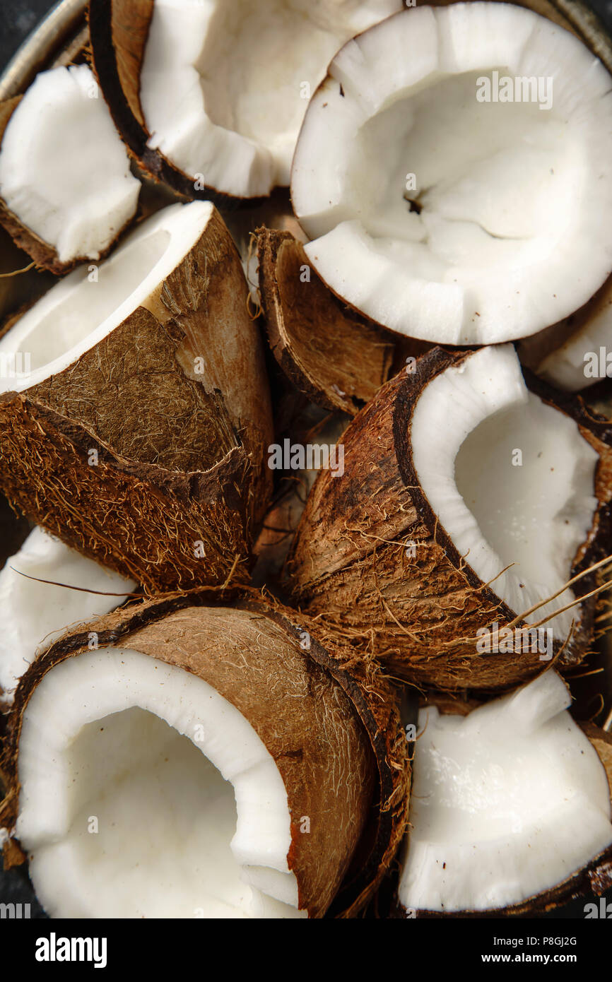 Close up view pf cracked coconuts arranged in metallic tray - Stock Image