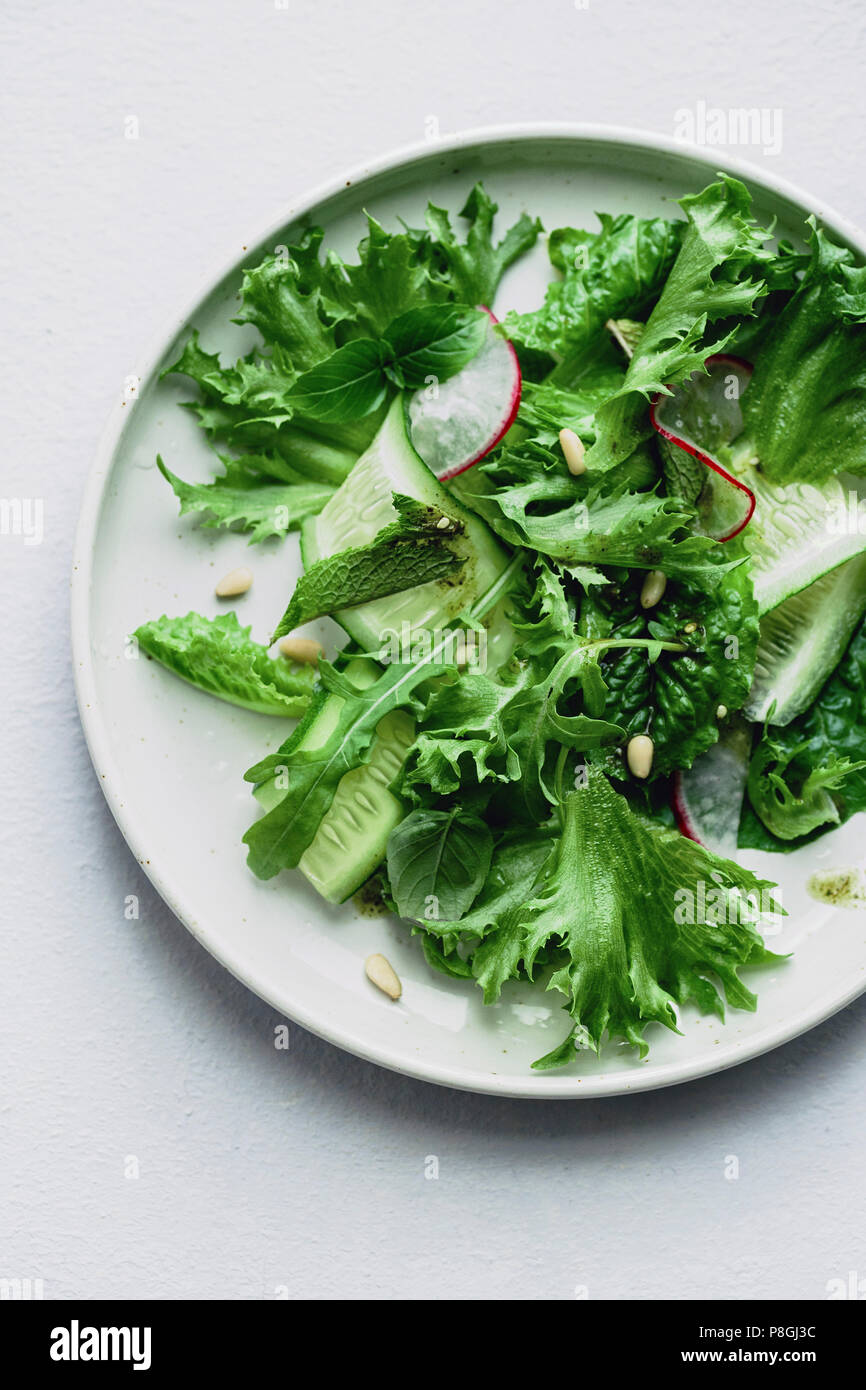 Overhead view of fresh green salad with radish and herbs on gray background - Stock Image