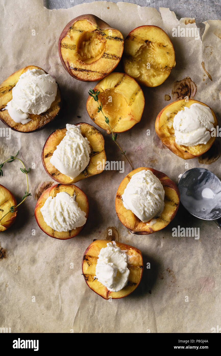 Melting vanilla ice cream served in hot grilled halved peaches and nectarines - Stock Image
