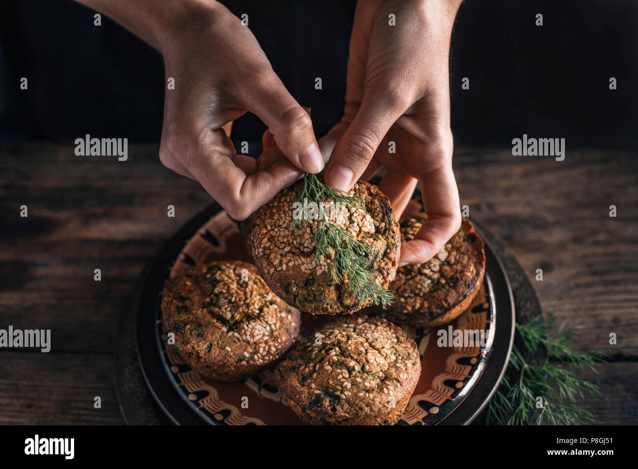 Persons Hands wth Corn muffins bread with leaf of chard - Stock Image