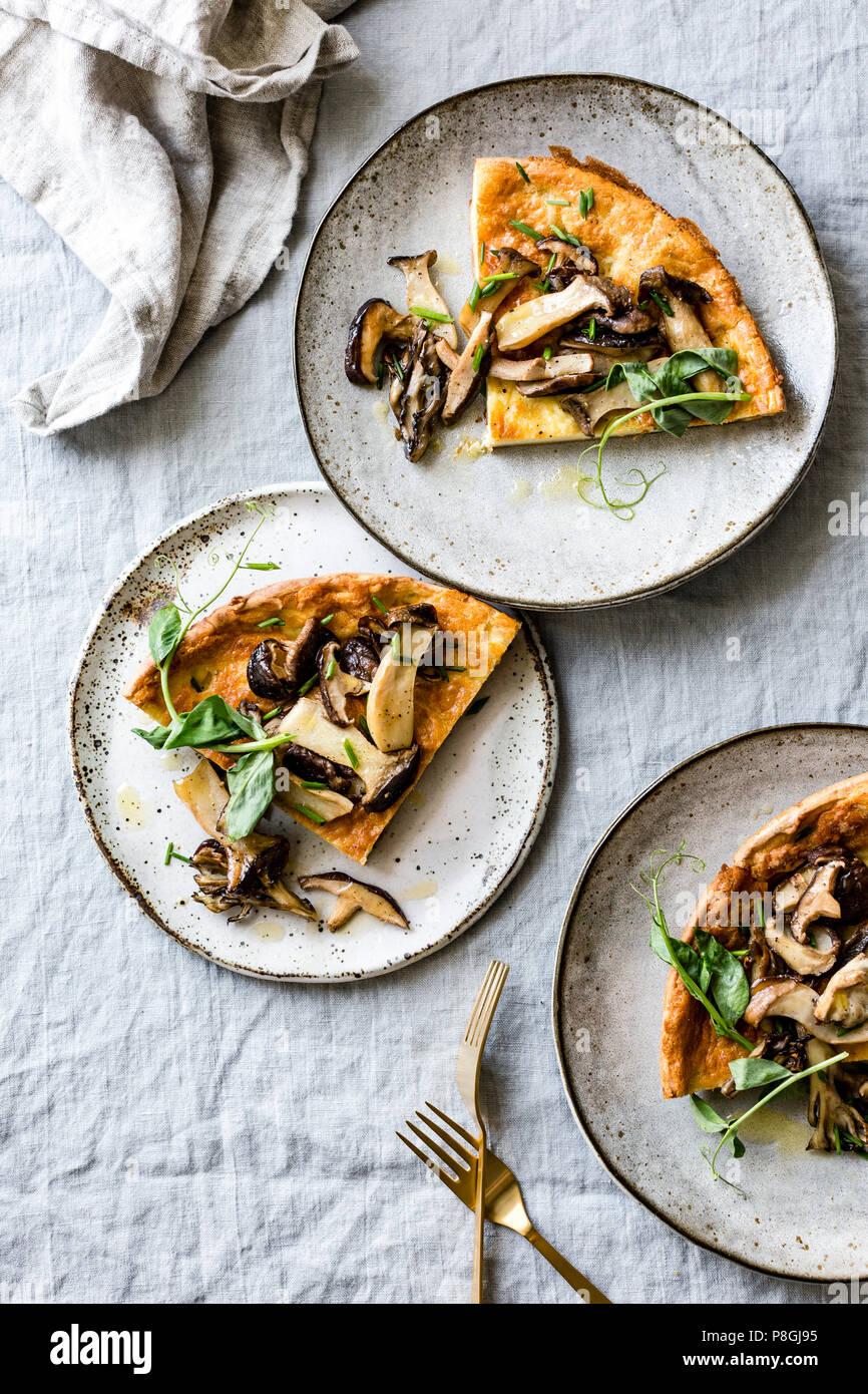 Wild Mushroom Savory Dutch Baby pancake with Pea Greens Stock Photo