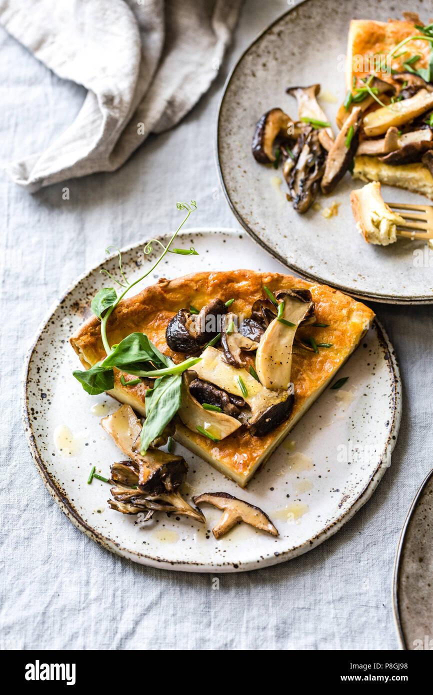 Wild Mushroom Savory Dutch Baby pancake with Pea Greens - Stock Image