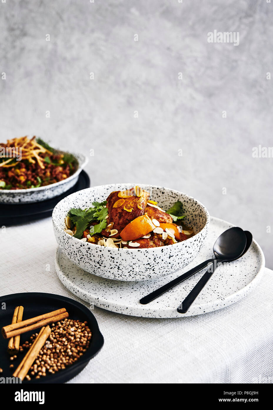Chicken and persimmon tagine with almonds, coriander. side dish of red rise and chickpeas with fried onions with fresh herbs. - Stock Image