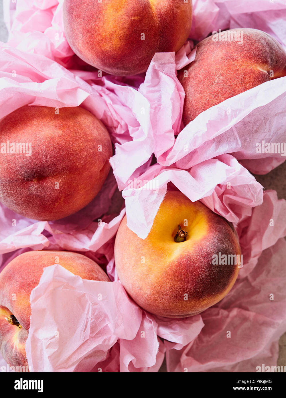 Fresh Peaches in Pink Tissue - Stock Image