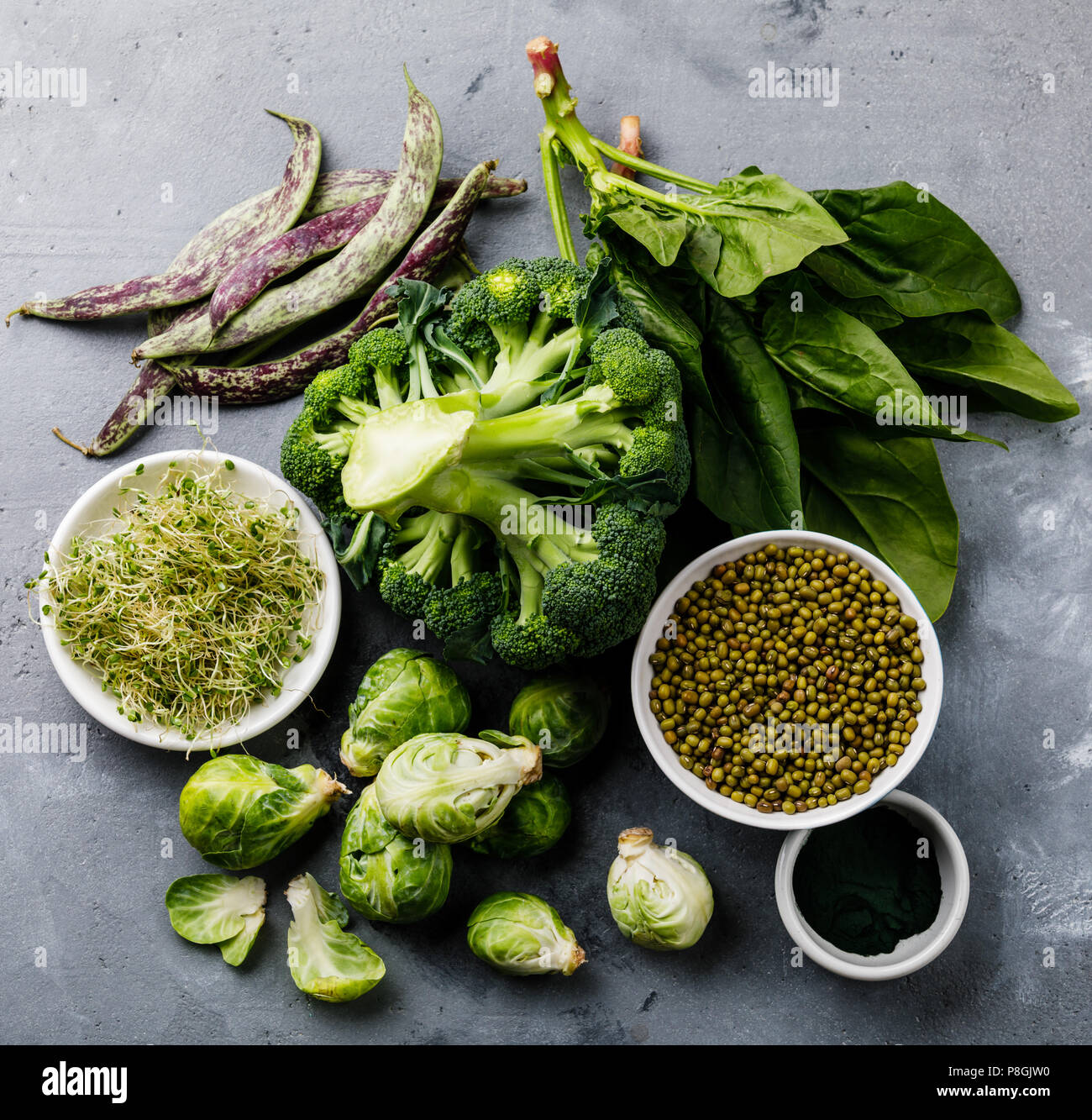 Healthy Green food Clean eating selection Protein source for vegetarians: brussels sprouts, broccoli, spinach, spirulina on gray concrete background - Stock Image