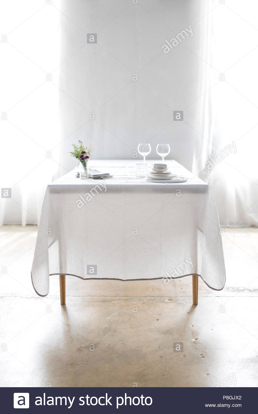 Long dinner table set with a white tablecloth and white plates against a bright, white, textured wall. - Stock Photo
