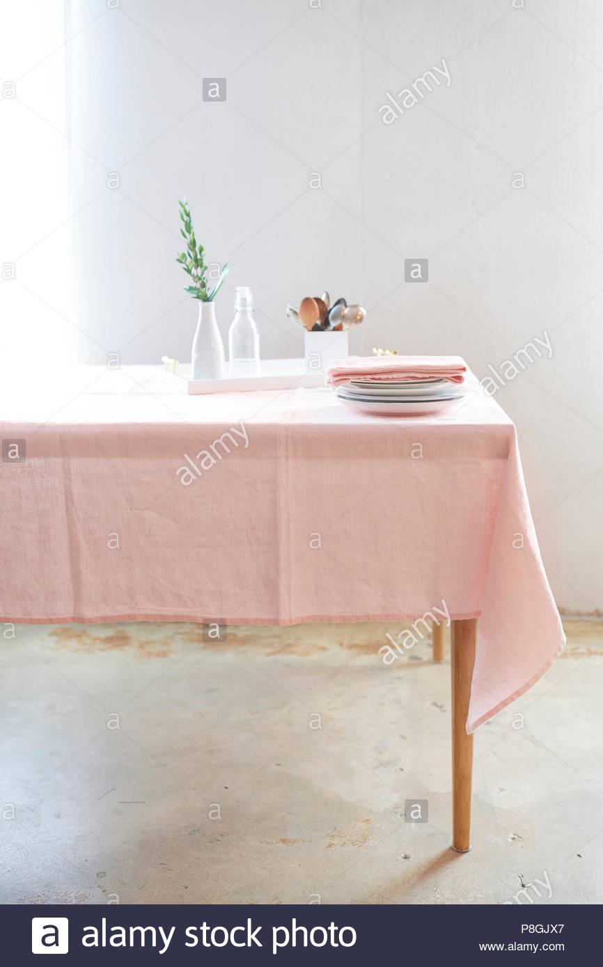 Long table set with a pale pink table cloth, plates and linens. Brightly lit against a textured white wall and concrete floors. - Stock Image