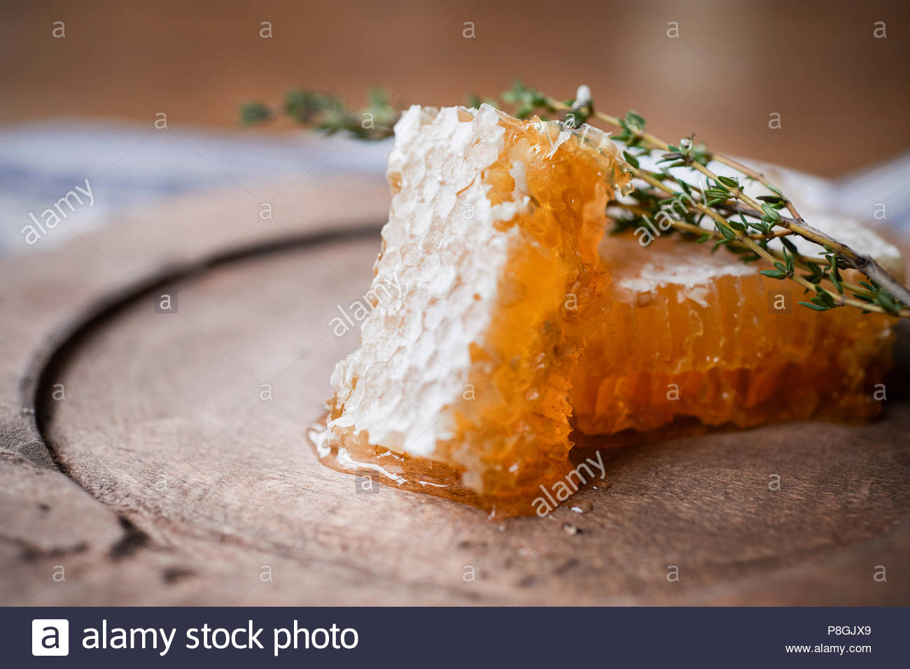 2 large pieces of honeycomb with fresh thyme on a rustic wood plate. - Stock Image