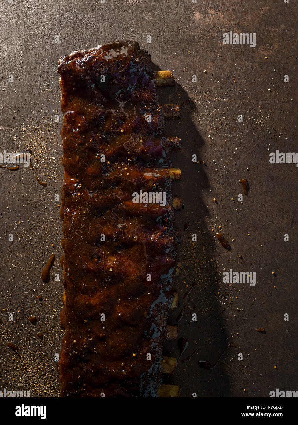 A long rack of ribs covered in sauce and seasonings on a brown surface with messy sprinkled spices around. - Stock Image