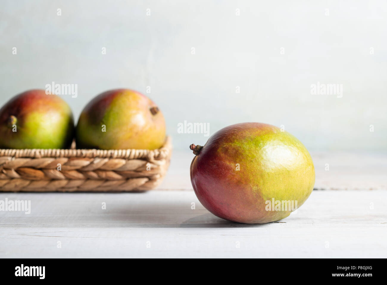 Three ripe mangoes in a wicker basket on a whitewash wood table with bright, natural light. - Stock Image