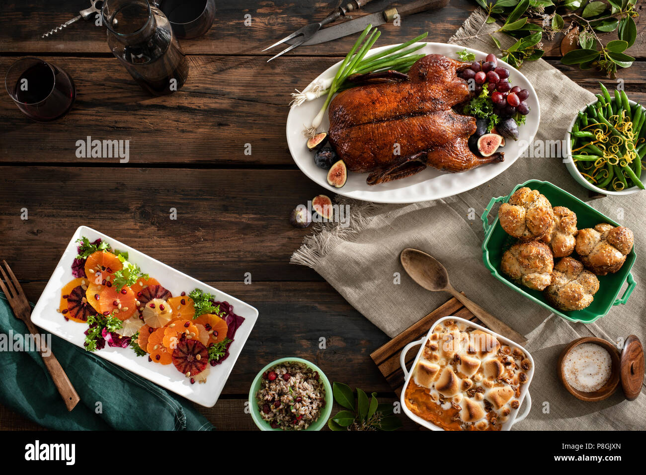 An overhead view of a holiday dinner with roasted duck, citrus salad, rice, green beans, rolls, sweet potato casserole and wine. Warm, moody tones on  - Stock Image