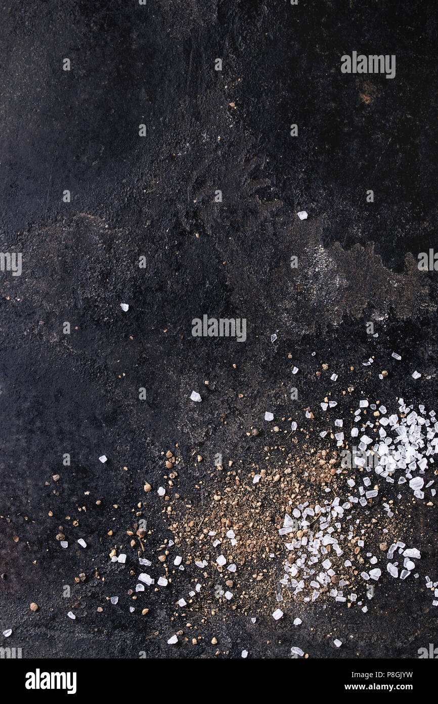 Groung black pepper powder and sea salt over old black iron texture surface. Top view, space. Food background - Stock Image
