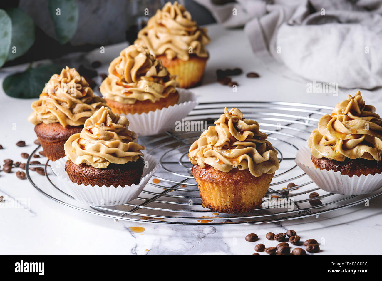 Fresh baked homemade cupcakes with coffee buttercream and caramel standing on cooling rack with eucalyptus branch and coffee beans above over white ma - Stock Image