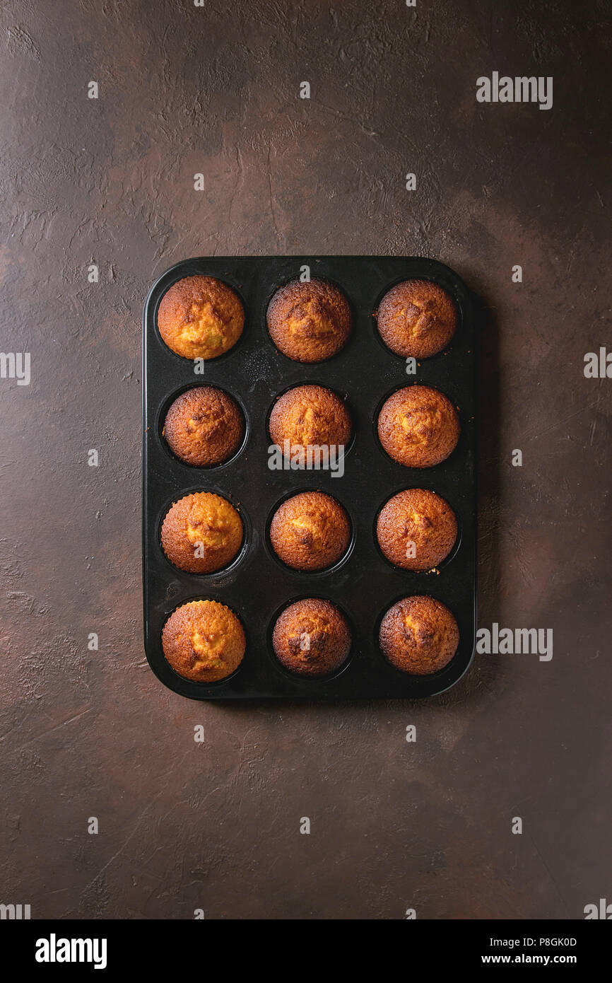 Fresh baked homemade lemon cakes muffins in black teflon baking dish over dark texture background. Top view, space. - Stock Image